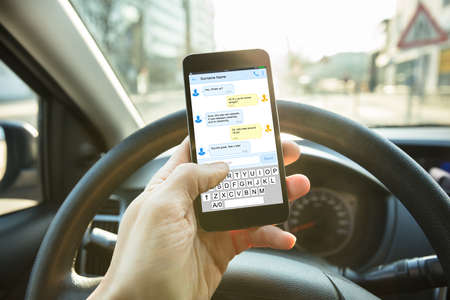 Photo for Close-up Of A Person Sending A Text Message Using Mobile Phone While Driving A Car - Royalty Free Image