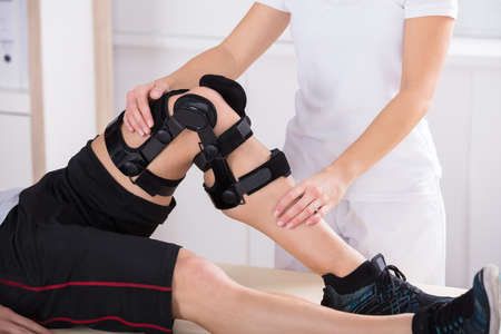 Photo pour Close-up Of A Female Physiotherapist Giving Leg Exercise In Clinic - image libre de droit