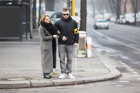 Photo pour Young Woman Assisting Blind Man With White Stick On Street - image libre de droit