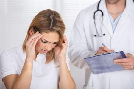 Foto de Female Patient With Headache In A Clinic - Imagen libre de derechos