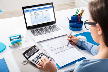 Photo pour Close-up Of A Businesswoman Calculating Invoice Using Calculator With Online Banking On Laptop Screen - image libre de droit