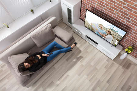 Foto de Elevated View Of A Woman Lying On Couch Watching Television At Home - Imagen libre de derechos