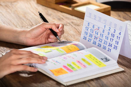 Photo pour Close-up Of A Businessperson With Calendar Writing Schedule In Diary On Desk - image libre de droit