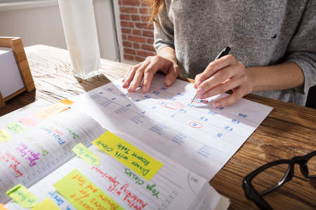 Photo pour Close-up Of A Businesswoman Marking Schedule On Calendar From Diary At Workplace - image libre de droit