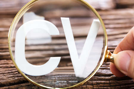 Photo for A Person Looking At White CV Word Through Magnifying Glass - Royalty Free Image