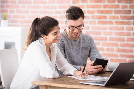 Foto de Happy Young Couple Calculating Bills At Home Using Calculator And Laptop - Imagen libre de derechos
