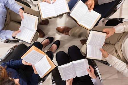 Photo for Elevated View Of People Sitting On Chair In Circle Reading Books - Royalty Free Image