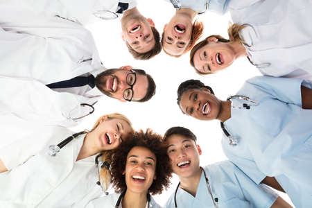 Photo for Low Angle View Of Smiling Medical Team Standing Against White Background - Royalty Free Image