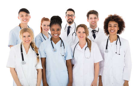 Foto de Portrait Of Smiling Multiracial Medical Team In Front Of White Background - Imagen libre de derechos