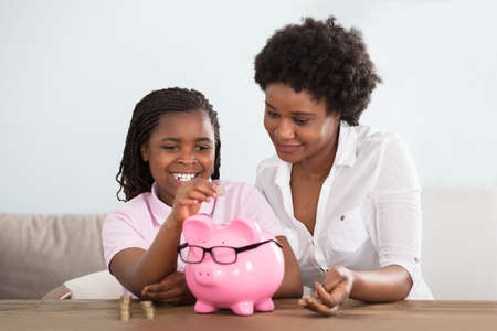 Foto de An African Girl Sitting With Her Mother Inserting Coins In Pink Piggy Bank At Home - Imagen libre de derechos