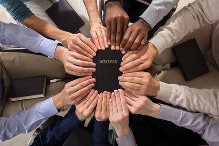 Foto de Overhead View Of Hands Holding Holy Bible - Imagen libre de derechos