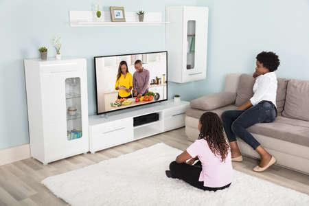 Foto de Mother And Daughter Watching Enjoying Watching Television At Home - Imagen libre de derechos