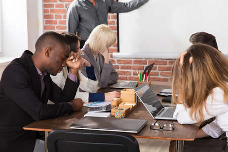 Foto de Diverse tired young business people bored during meeting in office - Imagen libre de derechos