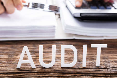 Photo for Close-up Of White Audit Text In Front Of Auditor Calculating Invoice - Royalty Free Image