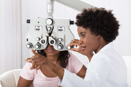 Photo pour Female African Optometrist Doing Sight Testing For Patient In Hospital - image libre de droit