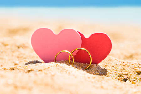Photo pour Two Heart Shapes With Golden Rings On Sand At Beach In Summer - image libre de droit