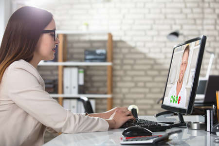 Foto de Young Businesswoman Doing Video Conference On Computer At Workplace In Office - Imagen libre de derechos