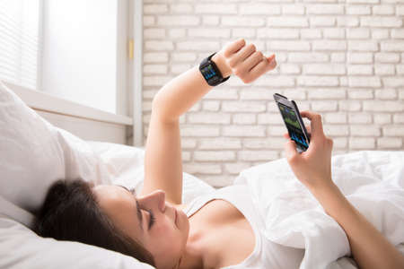 Photo pour Close-up Of A Young Woman Lying On Bed Synchronizing Smart Watch With Cell Phone - image libre de droit
