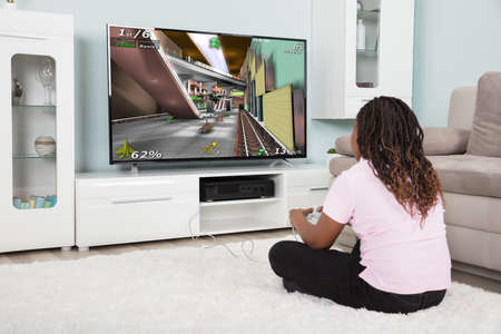 Photo pour Rear View Of An African Girl Playing Video Games At Home - image libre de droit