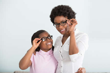 Portrait Of A Smiling Daughter And Mother With Eyeglasses Against White Background