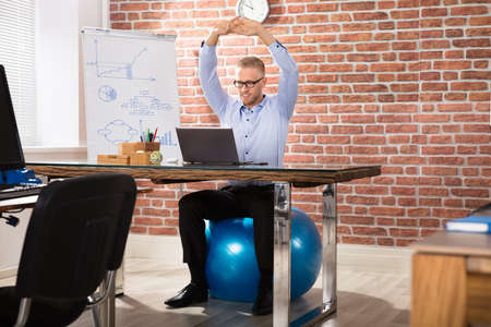Photo pour Close-up Of A Happy Businessman Relaxing On Fitness Ball In Office - image libre de droit
