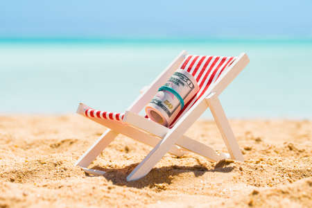 Photo pour Rolled Up Bundle Of Fifty Dollar Banknotes On Miniature Deck Chair At Beach - image libre de droit
