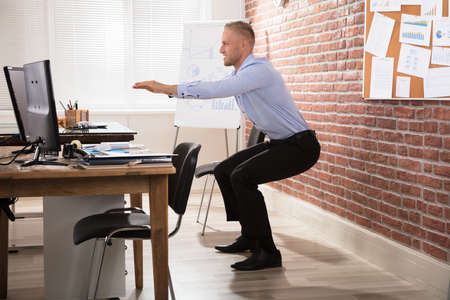 Photo pour Happy Businessman Doing Exercise In Front Of Computer At Office - image libre de droit