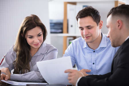 Photo pour Couple Talking With Advisor During Meeting In Office - image libre de droit