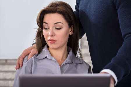 Photo pour A Boss Touching The Shoulder Of Female Colleague In Workplace At Office - image libre de droit
