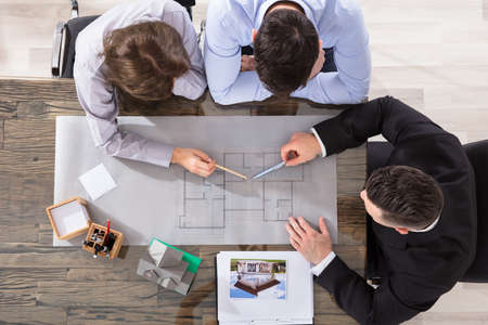 Photo pour Elevated View Of Architect Working On Blueprint With Couple - image libre de droit