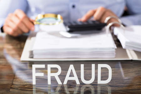 Photo for Close-up Of Financial Data Analyst With Fraud Text On Glass Desk In Office - Royalty Free Image