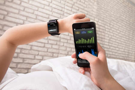 Foto per Woman's Hand Showing Heart Rate On Smart Watch And Cell Phone - Immagine Royalty Free