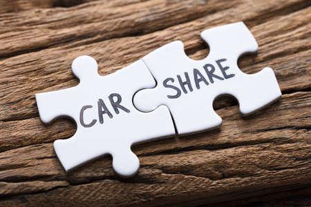 Foto de Closeup of connected car share jigsaw pieces on wood - Imagen libre de derechos