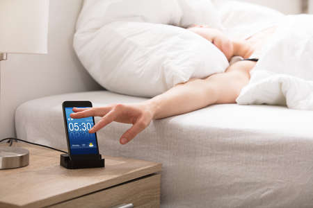 Photo pour Woman Sleeping On Bed Snoozing Alarm On Smart Phone Screen - image libre de droit