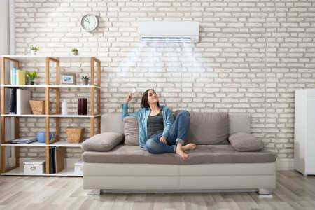 Foto de Happy Young Woman Holding Remote Control Relaxing Under The Air Conditioner - Imagen libre de derechos