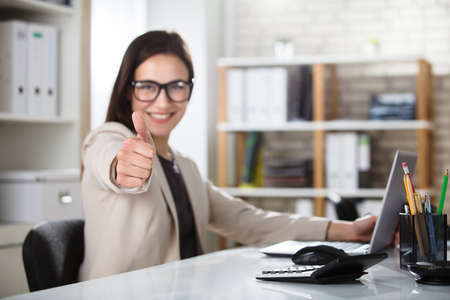 Photo for Portrait Of A Smiling Young Businesswoman Showing Thumbs Up - Royalty Free Image