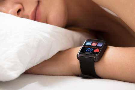 Photo pour Smart Watch Showing Heartbeat Rate On Sleeping Woman's Hand - image libre de droit