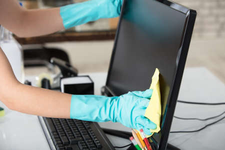 Photo for Close-up Of A Woman's Hand Cleaning The Desktop Screen With Yellow Rag In Office - Royalty Free Image