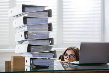 Photo for Young Businesswoman Peering At The Stack Of Folders In Curiosity From Behind The Desk - Royalty Free Image