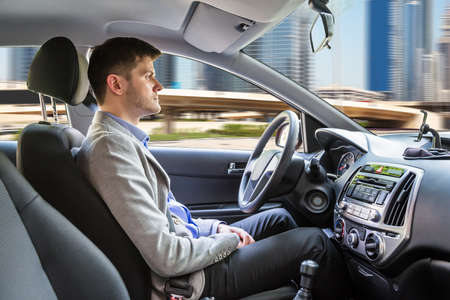 Photo pour Side View Of A Young Man Sitting Inside Autonomous Car - image libre de droit