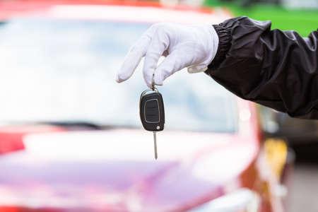 Photo pour Close-up Of A Valet Wearing Glove Holding Car Key - image libre de droit