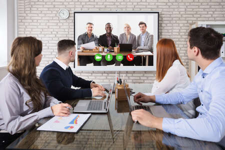 Photo for Group Of Business People Doing Video Conferencing In Business Meeting At Office - Royalty Free Image