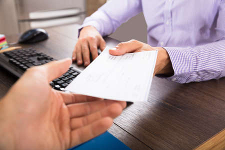 Photo pour Close-up Of A Businessman Giving Cheque To Her Colleague At Workplace In Office - image libre de droit