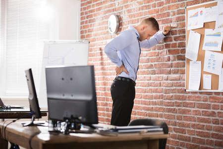 Foto de Businessman Leaning Against The Brick Wall Having Back Pain In Office - Imagen libre de derechos