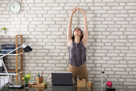 Photo for Young Businesswoman Stretching At Workplace In Office - Royalty Free Image