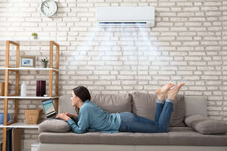Photo pour Woman Lying On Sofa Using Laptop Enjoying The Cooling Of Air Conditioner At Home - image libre de droit