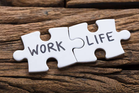 Foto de Closeup of work and life words written on pieces of jigsaw puzzle against wood - Imagen libre de derechos