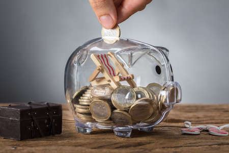 Foto de Closeup of hand putting coin in transparent piggy bank with deck chair - Imagen libre de derechos