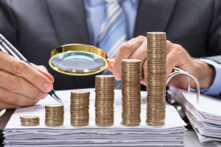 Photo for Businessman using magnifying glass to examine invoice with stacked coins arranged in increasing order - Royalty Free Image
