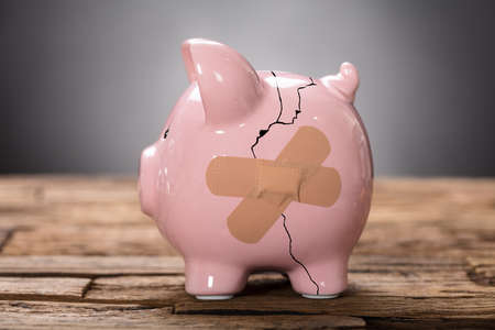 Photo pour Closeup of broken pink piggybank with bandage on wood - image libre de droit
